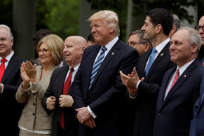 FILE: President Donald Trump, flanked by House Ways and Means Committee Chairman Rep. Kevin Brady, R-Texas, and House Speaker Paul Ryan of Wis., are seen in the Rose Garden of the White House in Washington, Thursday, May 4, 2017, after the House pushed through a health care bill.
