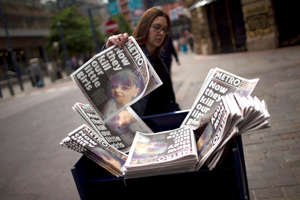 A woman picks a newspaper reporting the news on the suicide attack at a concert by Ariana Grande that killed more than 20 people as it ended Monday night in central Manchester, Britain, Wednesday, May 24, 2017.