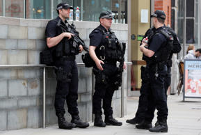 Armed police officers keep guard near the Arndale centre in Manchester, Wednesda...