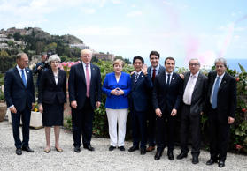 (L-R) The President of the European Council Donald Tusk, Britain's Prime Minister Theresa May, US President Donald Trump, German Chancellor Angela Merkel, Japanese Prime Minister Shinzo Abe, Canadian Prime Minister Justin Trudeau, French President Emmanuel Macron, the President of the European Commission Jean-Claude Juncker and Italian Prime Minister Paolo Gentiloni pose after watching an Italian flying squadron during the Summit of the Heads of State and of Government of the G7, the group of most industrialized economies, plus the European Union, on May 26, 2017 in Taormina, Sicily.
