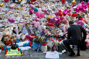 A man crouches in front of flowers, messages and tokens left in tribute to the victims of the attack on Manchester Arena, in central Manchester, Britain May 26, 2017. <br /><br /><br /><br /><br /><br /><br /><br /><br /><br /><br /><br /><br /><br /><br /><br /><br />
