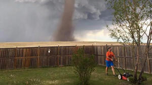 Stunning photo shows a man casually mowing his lawn as tornado looms