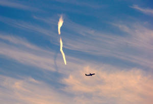 The trail of an aeroplane can be seen amongst clouds and above a plane after it took off from Sydney Airport, Sydney, Australia June 5, 2017.