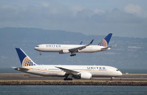 A United Airlines aircraft taxis as another lands at San Francisco International Airport, San Francisco, California, U.S., February 7, 2015.