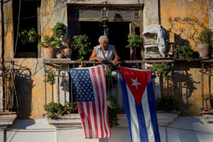 FILE - In this Dec. 19, 2014 file photo, Javier Yanez stands on his balcony decorated with U.S. and Cuban flags in Old Havana, Cuba. On Friday, June 16, 2017, President Donald Trump is expected to turn America's Cuba policy on its second 180-degree spin in three years. Ordinary Cubans are bracing for the worst.