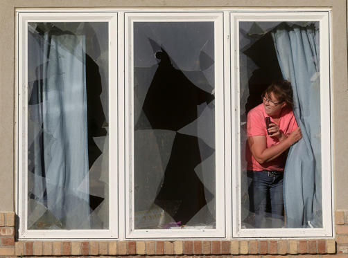 Slide 1 of 20: Amy Lounsbury looks out the broken window of a home after a tornado damaged it on Monday, June 12, 2017, near Carpenter. Severe storms spawned tornadoes and dropped large hail in parts of eastern Wyoming, injuring at least one person.