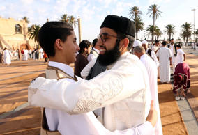 Libyan Muslims embrace following prayers on the first day of Eid al-Adha on Sept...