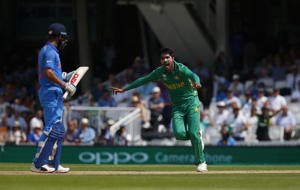 Mohammad Amir celebrates taking the wicket of Indian captain Virat Kohli.