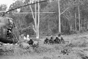 "U.S., paratroopers form up as they leap from helicopter for strike against Viet Cong controlled area 30 miles north of Saigon in Vietnam on June 29, 1965. The members of the 173rd airborne brigade joined up with Vietnamese paratroopers for the first joint combat operation of the war against the Viet Cong guerrillas. Area of operation is known as ""D"" zone and has been subjected to heavy bombing attacks."