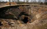 John Sparkman is dwarfed as he looks into a sinkhole near Picher, Okla., Saturday, April 6, 2008. Years of lead and zinc mining has left turned the town into a superfund site with sinkholes, lead-laced mountains of rock, and tainted water.