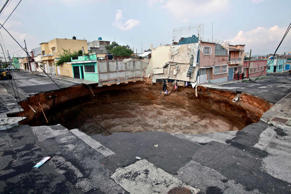 A sinkhole covers a street intersection in downtown Guatemala City,Tuesday, June 1, 2010.