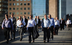 City Workers walk along London Bridge in the early morning sunshine