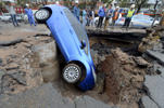 Workers look on as a car is stranded in a sinkhole on a street in Lanzhou, Gansu province, China, September 9, 2015. The driver managed to get out of the car unharmed and no one was injured during the incident, local media reported.