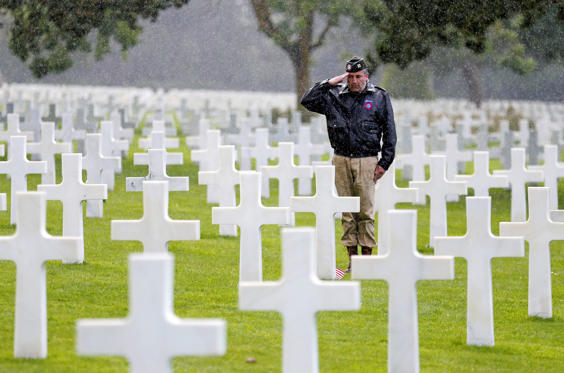 Slide 25 de 36: COLLEVILLE-SUR-MER , FRANCE - JUNE 06:  A man dressed in US military uniform pays tribute to a soldier during commemorations marking the 73th anniversary of D-Day, the June 6,1944 landings of Allied forces in Normandy at the American cemetery on June 06,