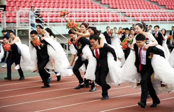 Slide 1 dari 36: Couples take part in a competition during a mass wedding of 64 doctoral student couples at Harbin Institute of Technology, a university in Harbin, Heilongjiang province, China, June 4, 2017. Picture taken June 4, 2017. REUTERS/Stringer ATTENTION EDITORS