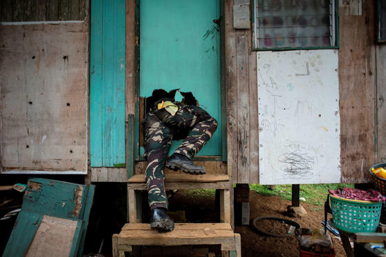 Slide 35 de 36: A soldier crawls through a hole through a door that he smashed during a house-to-house clearing operation against Islamist militants in Marawi, on the southern island of Mindanao on June 7, 2017. With bomb-proof tunnels, anti-tank weapons hidden in mosques, human shields and a 'mastery' of the terrain, Islamist militants holed up in a southern Philippine city are proving a far tougher opponent than military chiefs expected.
