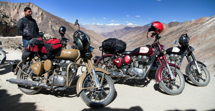 Slide 1 of 11: Motocycles brand Royal Enfield and biker in highest road pass on the world Khardung La, Ladakh, Jammu and Kashmir, India