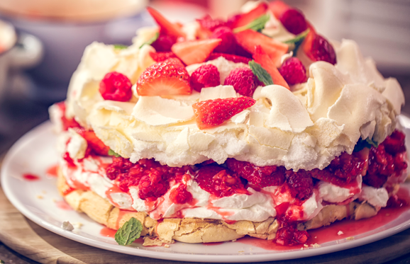Slide 1 of 48: Delicious Berry Pavlova Cake with fresh strawberries, raspberries, mint leaves and whipped cream.