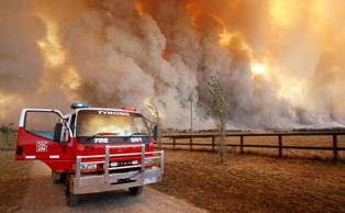 A Country Fire Authority (CFA) staff monitor a giant fire raging in the Bunyip State Park near Labertouche, some 125 kilometres west of Melbourne, on February 7, 2009. More than 40 blazes raged across two states as a once-in-a-century heatwave pushed the mercury as high as 46 degrees Celsius (115 Fahrenheit) with fire bans in place across much of the south-east, with conditions said to be the worst since the Ash Wednesday wildfires of 1983, which killed 75 people and razed 2,500 homes. AFP PHOTO/William WEST (Photo credit should read WILLIAM WEST/AFP/Getty Images)