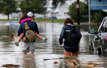 Don Noel carries his daughter Alexis, 8, with his wife Lauren, right, as they walk through a flooded roadway to check on their boat in the West End section of New Orleans on June 21.