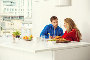 Young couple sitting in the modern kitchen in the morning and having breakfast.