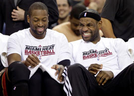 Miami Heat's Dwayne Wade,left, and LeBron James sit together on the bench in the closing moments of their NBA basketball game against the Sacramento Kings in Sacramento, Calif., Saturday, Jan. 12, 2013.