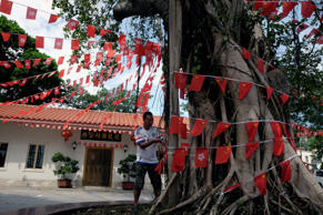 A villager hangs Chinese national flags and Hong Kong flags to a tree to celebrate the upcoming 20th anniversary of the territory's handover to Chinese rule, in Hong Kong, China June 24, 2017.