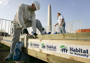 "Volunteers works on building a wall as part of the ""Habitat for Humanity"" project."