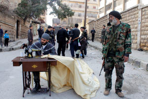A Free Syrian Army fighter sews cloth in Aleppo February 24, 2013. REUTERS/Hamid Khatib (SYRIA - Tags: CONFLICT POLITICS CIVIL UNREST) - RTR3E82Q