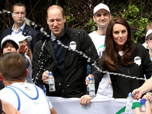 A runner squirts water towards Prince William and Catherine Duchess of Cambridge on April 23,  2017.