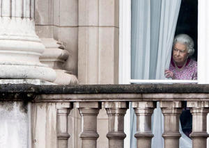 Queen Elizabeth II peers through the curtains of Buckingham Palace as she waits for The Patrons Lunch to start on The Mall 12 Jun 2016