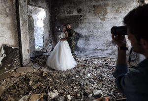TOPSHOT - Newly-wed Syrian couple Nada Merhi,18, and Hassan Youssef,27, have their wedding pictures taken in a heavily damaged building in the war ravaged city of Homs on February 5, 2016. A Syrian photographer thought of using the destruction of Homs to take pictures of newly wed couples to show that life is stronger than death. / AFP / JOSEPH EID (Photo credit should read JOSEPH EID/AFP/Getty Images)