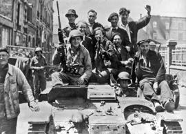 After liberation, victorious American soldiers and jubilant French civilians, atop a captured German tank, as they drive along the streets, Cherbourg, France, June 26, 1944. (Photo by Interim Archives/Getty Images)