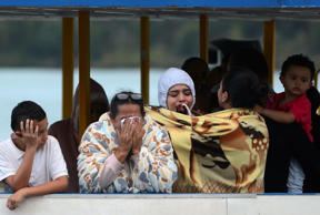 People who survived the capsizing of a ferry, cry as they wait for more informat...