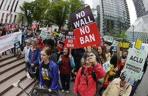 In this May 15, 2017 file photo, protesters wave signs and chant during a demonstration against President Donald Trump's revised travel ban, outside a federal courthouse in Seattle. The Supreme Court is letting the Trump administration enforce its 90-day ban on travelers from six mostly Muslim countries, overturning lower court orders that blocked it. The action Monday, June 26, 2017, is a victory for President Donald Trump in the biggest legal controversy of his young presidency.