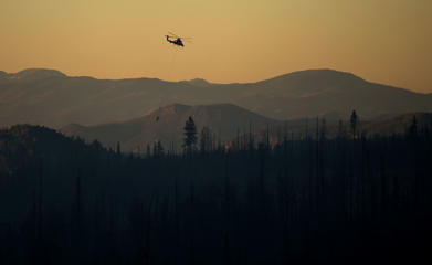 In this June 18, 2017, photo, helicopter crews put out hot spots as night falls in Utah. Firefighters in Utah were battling a wildfire Monday that shut down a highway and forced hundreds of people to flee a ski town as crews in New Mexico mop up another blaze amid scorching heat in the Southwest U.S.