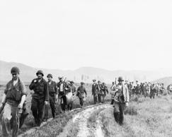 American troops, members of the Korean military advisory group, march toward Kim...