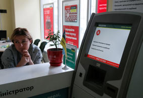 An employee sits next to a payment terminal out of order at a branch of Ukraine's state-owned bank, Oschadbank, in Kiev after Ukrainian institutions were hit by cyber attacks on Tuesday.