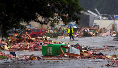 A police officer stands guard after a possible tornado touched down destroying several businesses, Thursday, June 22, 2017, in Fairfield, Ala. Alabama Gov. Kay Ivey says the threat of severe weather has not concluded as the remnants of Tropical Storm Cindy pushes inland. Ivey in a Thursday press briefing urged people to stay vigilant.