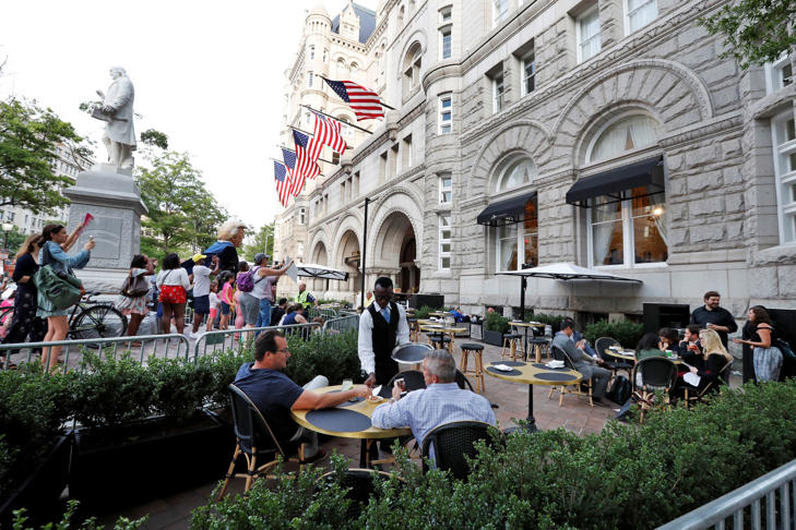 Protesters yell at patrons at the outdoor seating area at the Trump International Hotel, Wednesday, June 28, 2017, in Washington. President Donald Trump is attending a fundraiser at the hotel.