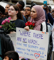 Mourners hold signs and flowers as they listen to speakers Wednesday, June 21, 2017, in Reston, Va., during a vigil in honor of Nabra Hassanen, who was killed over the weekend. Islamic leaders are questioning Virginia detectives' insistence that the beating death of Nabar appears to have been a case of road rage, saying the attack looks all too much like a hate crime
