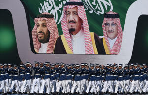Saudi air force officers march in front of a banner bearing portraits of King Salman bin Abdulaziz, center, Prince Mohammed bin Nayef, right, and Prince Mohammed bin Salman in Riyadh in January.