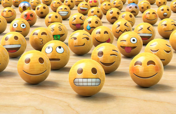 Slide 1 of 15: Many wooden emoticon or Emoji face balls, one up front
