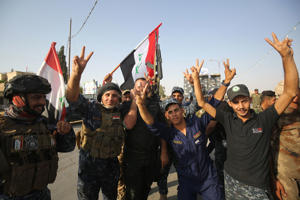 Iraqi federal police members flash the sign for victory as they celebrate in the Old City of Mosul on July 9, 2017 after the government's announcement of the 'liberation' of the embattled city.