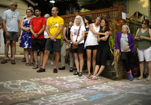 People listen as Bethany Bradley of Women's March Minnesota speaks at the beginning of a vigil to remember Justine Damond, from Sydney, Australia, who was shot and killed late Saturday by police, Sunday evening, July 16, 2017 in Minneapolis.