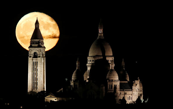 Slide 1 of 32: The moon rises over the Sacre Coeur Basilica in Montmartre in Paris, France, November 5, 2017.