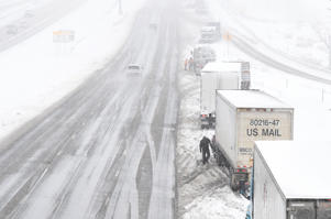 Truck drivers stop to chain-up on Interstate 70 as a spring snow storm continues to drop snow in the area in April in Golden, Colorado.