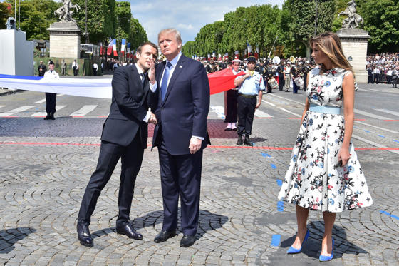 Bild 3 av 27: French President Emmanuel Macron (L) shakes hands with US President Donald Trump, next to US First Lady Melania Trump, during the annual Bastille Day military parade on the Champs-Elysees avenue in Paris on July 14, 2017. The parade on Paris's Champs-Elysees will commemorate the centenary of the US entering WWI and will feature horses, helicopters, planes and troops. / AFP PHOTO / POOL AND AFP PHOTO / CHRISTOPHE ARCHAMBAULT (Photo credit should read CHRISTOPHE ARCHAMBAULT/AFP/Getty Images)