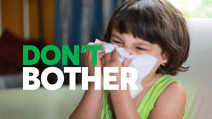 a young child holding a sign: Don't Bother Giving Kids Cough and Cold Medicines