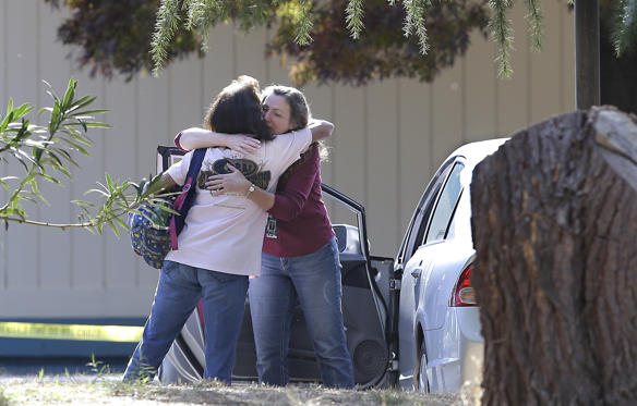 Two women embrace outside Rancho Tehama Elementary School, where a gunman opened fire Tuesday, Nov. 14, 2017, in Corning, Calif. Authorities said, a gunman choosing targets at random, opened fire in a rural Northern California town Tuesday, killing four people at several sites and wounding others at the elementary school before police shot him dead.